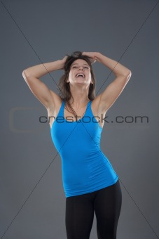 energetic young woman with blue top dancing - isolated on gray background