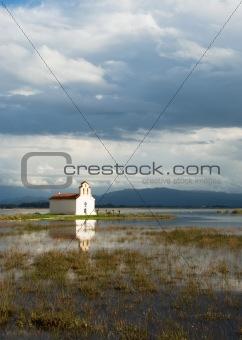 Greek church on a lake and deep blue sky