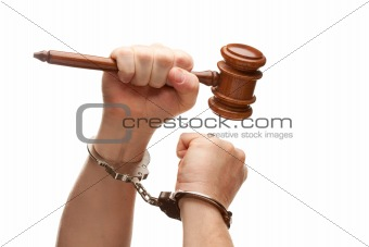 Handcuffed Man Holding Wooden Gavel in His Fist Isolated on a White Background.