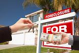 Handing Over Cash For House Keys in Front of House and Foreclosure Sign.