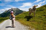 Girl and cow in Alps