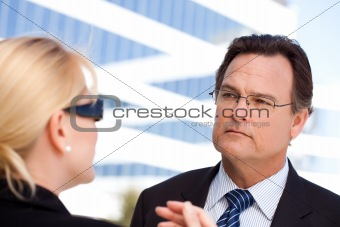 Attentive Handsome Businessman in Suit and Tie Listens to Female Colleague Outdoors.