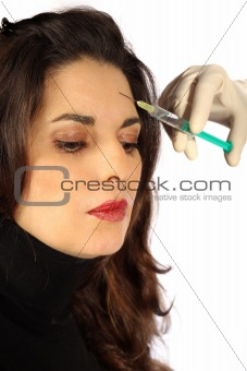 Young woman receives botox injection in her forehead