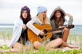 Three Young Women Sitting on Chilly Beach With Guitar