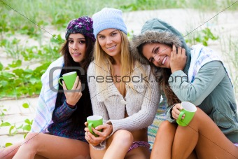 Three Friends Bundled Up With Coffee Cups at the Beach
