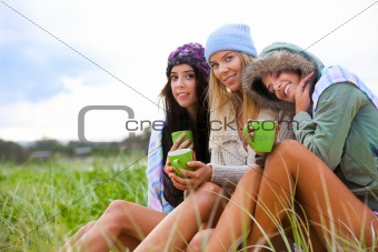 Three Friends Bundled Up With Coffee Cups in the Grass