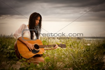 Attractive Young Woman With Guitar on Beach