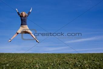 A pretty woman jumps for joy in a field