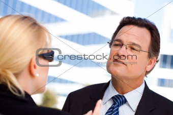 Attentive, Handsome Businessman in Suit and Tie Talking with Female Colleague Outdoors.