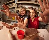 Cute young girls in a clay studio holding up their hands