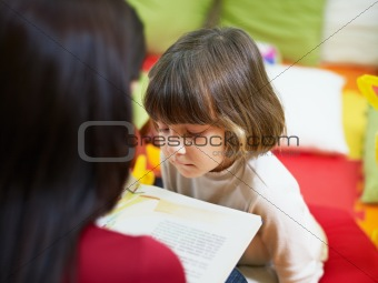 female teacher reading book to little girl