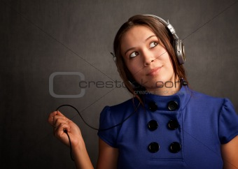 Pretty young woman in a blue dress with Headphones