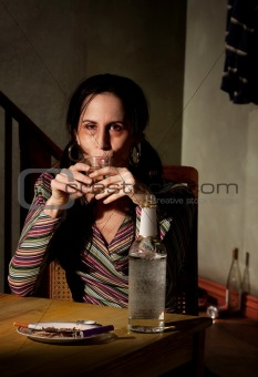 Alcoholic woman with bottle of clear liquor