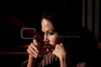 Alcoholic woman with glass of clear liquor