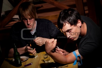 Two men with heroin cooking in a bent spoon