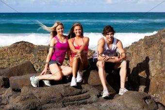 Three People on Rocks at the Beach