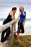 Smiling Young Couple By Fence at the Beach