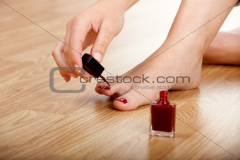 Applying red nail polish