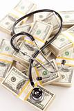 Question Mark Shaped Stethoscope Laying on Stacks of Hundred Dollar Bills with Narrow Depth of Field.