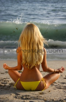 Beautiful Blond Meditating on the beach at Sunset