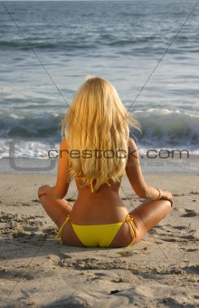 Beautiful Blond sitting on the beach at Sunset looking at the Oc