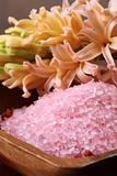 Pink bath salt in a wooden bowl