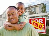 Happy African American Father and Son in Front of New Home and Real Estate Sign.