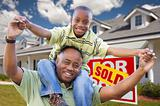 Happy African American Father and Son in Front of New Home and Sold Real Estate Sign.