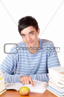 Young happy handsome male student sitting on desk learning with