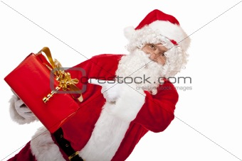 Old Santa Claus holding Christmas gift and pointing with finger