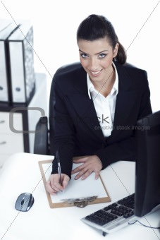 Business woman making notes and looking at the camera up