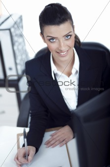 Attractive woman writing on clipboard