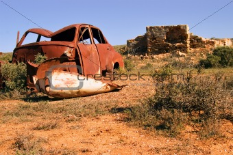 an old rusting car and ruins in the desert