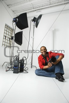 Young male sitting on studio floor with camera.
