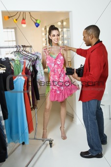 Young male photographer holding dress up to young female model.