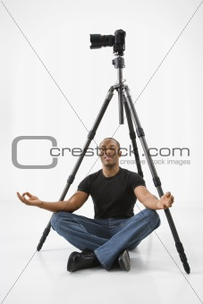 Young male adult meditating under camera and tripod.
