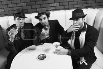 Three retro businessmen sitting at table with cocktails.