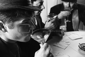 Three retro businessmen drinking cocktails.