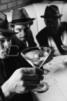 Three retro businessmen sitting at table with martini.
