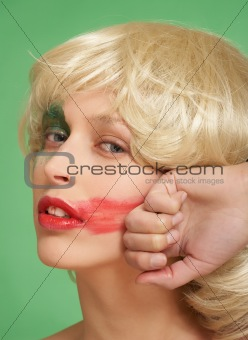 A beautiful girl in a wig. She smears lipstick on the face