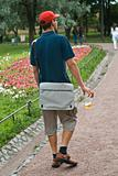 young man walking with a beer