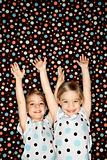 Female children twins  with arms raised.