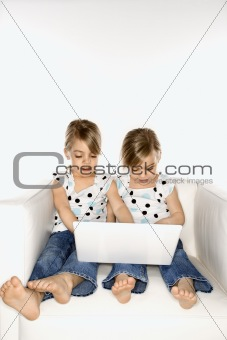 Female children twins playing with laptop computer.