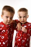 Male twin children leaning on eachother.
