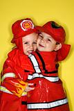 Caucasian twin boys dressed as firemen.