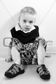 Caucasian boy sitting on floor.