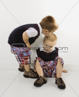 Caucasian twin boy kissing other twin boy on head.