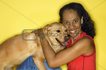 Adult female petting dog.