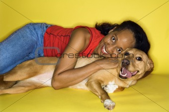 Adult female hugging dog.