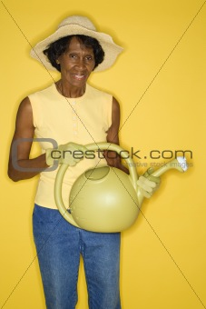 Mature adult female holding watering can.